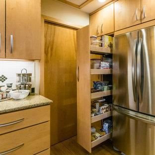 На фото: отдельная, п-образная кухня среднего размера в стиле ретро с врезной раковиной, плоскими фасадами, светлыми деревянными фасадами, гранитной столешницей, белым фартуком, фартуком из керамической плитки, техникой из нержавеющей стали, полом из бамбука и островом