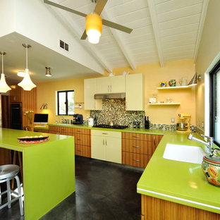 Photo of a contemporary l-shaped eat-in kitchen in Los Angeles with flat-panel cabinets, medium wood cabinets, multi-coloured splashback, mosaic tile splashback, quartz benchtops, stainless steel appliances, concrete floors, a peninsula, an undermount sink and green benchtop.