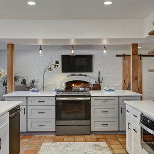 フェニックスの中サイズのミッドセンチュリースタイルのおしゃれなキッチン (アンダーカウンターシンク、シェーカースタイル扉のキャビネット、白いキャビネット、珪岩カウンター、マルチカラーのキッチンパネル、メタルタイルのキッチンパネル、シルバーの調理設備の、テラコッタタイルの床、赤い床、白いキッチンカウンター) の写真