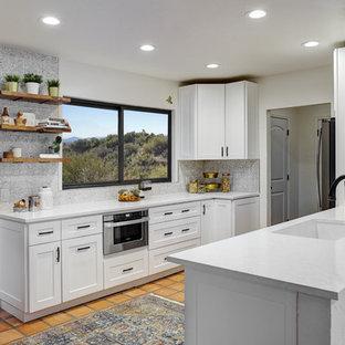 フェニックスの中くらいのミッドセンチュリースタイルのおしゃれなキッチン (アンダーカウンターシンク、シェーカースタイル扉のキャビネット、白いキャビネット、珪岩カウンター、マルチカラーのキッチンパネル、メタルタイルのキッチンパネル、シルバーの調理設備、テラコッタタイルの床、赤い床、白いキッチンカウンター) の写真