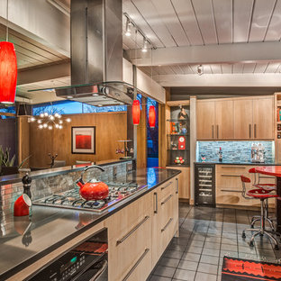 This is an example of a mid-sized midcentury galley open plan kitchen in Denver with an undermount sink, flat-panel cabinets, light wood cabinets, quartz benchtops, metallic splashback, metal splashback, black appliances, porcelain floors and with island.