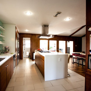 Design ideas for a mid-sized midcentury single-wall eat-in kitchen in Houston with a double-bowl sink, beaded inset cabinets, medium wood cabinets, laminate benchtops, stainless steel appliances, limestone floors and with island.