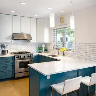 ポートランドの中サイズのミッドセンチュリースタイルのおしゃれなキッチン (アンダーカウンターシンク、シェーカースタイル扉のキャビネット、青いキャビネット、珪岩カウンター、白いキッチンパネル、サブウェイタイルのキッチンパネル、シルバーの調理設備の、リノリウムの床、オレンジの床) の写真