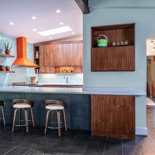 Inspiration för mellanstora retro grått kök, med en enkel diskho, släta luckor, skåp i mellenmörkt trä, bänkskiva i kvarts, stänkskydd i keramik, färgglada vitvaror, klinkergolv i keramik, en köksö och svart golv