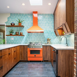 Example of a mid-sized 1960s u-shaped ceramic floor and black floor kitchen design in Cincinnati with a single-bowl sink, flat-panel cabinets, quartz countertops, ceramic backsplash, colored appliances, an island, gray countertops, dark wood cabinets and blue backsplash