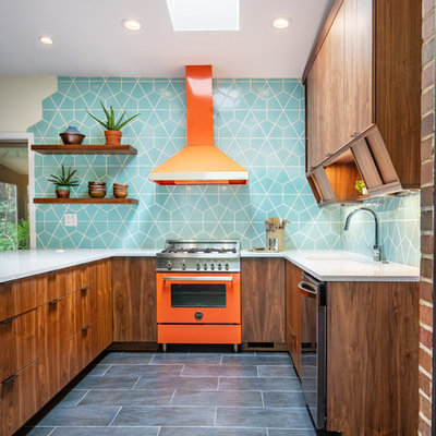 Example of a mid-sized 1960s u-shaped ceramic tile and black floor kitchen design in Cincinnati with a single-bowl sink, flat-panel cabinets, quartz countertops, ceramic backsplash, colored appliances, an island, gray countertops, dark wood cabinets and blue backsplash