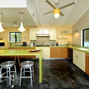 ロサンゼルスの中サイズのコンテンポラリースタイルのおしゃれなキッチン (アンダーカウンターシンク、フラットパネル扉のキャビネット、中間色木目調キャビネット、クオーツストーンカウンター、マルチカラーのキッチンパネル、モザイクタイルのキッチンパネル、シルバーの調理設備の、コンクリートの床、黒い床、緑のキッチンカウンター) の写真