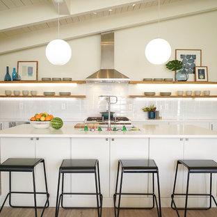 На фото: п-образная кухня в стиле ретро с врезной раковиной, плоскими фасадами, белыми фасадами, белым фартуком, техникой из нержавеющей стали, паркетным полом среднего тона, островом, коричневым полом и белой столешницей с