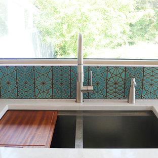 Imagen de cocina minimalista con fregadero bajoencimera, armarios con paneles lisos, encimera de cuarcita, salpicadero azul, salpicadero de azulejos de cerámica, electrodomésticos de acero inoxidable y suelo de baldosas de porcelana