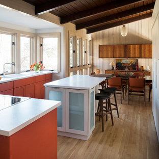 Imagen de cocina comedor en L, retro, de tamaño medio, con armarios estilo shaker, puertas de armario naranjas, encimera de acrílico, una isla, fregadero de doble seno, electrodomésticos de acero inoxidable y suelo de madera clara