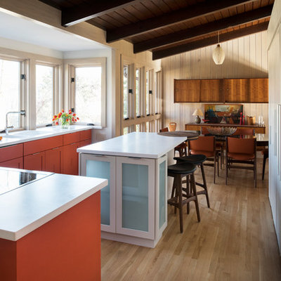 Inspiration for a mid-sized 1950s l-shaped light wood floor eat-in kitchen remodel in Atlanta with shaker cabinets, orange cabinets, solid surface countertops, an island, a double-bowl sink and stainless steel appliances