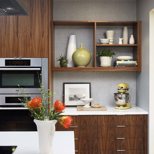 Inspiration for a mid-sized midcentury l-shaped eat-in kitchen in San Francisco with an undermount sink, flat-panel cabinets, medium wood cabinets, quartzite benchtops, white splashback, ceramic splashback, stainless steel appliances and with island.