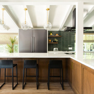 Design ideas for a midcentury l-shaped kitchen in Los Angeles with an undermount sink, shaker cabinets, medium wood cabinets, green splashback, stainless steel appliances, medium hardwood floors, with island, brown floor and white benchtop.