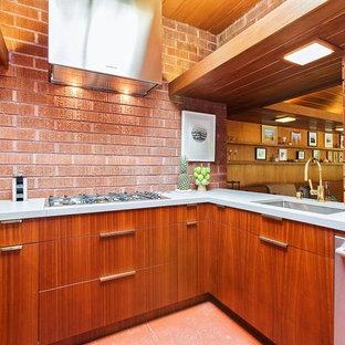 サンフランシスコの小さいモダンスタイルのおしゃれなキッチン (アンダーカウンターシンク、フラットパネル扉のキャビネット、中間色木目調キャビネット、クオーツストーンカウンター、茶色いキッチンパネル、レンガのキッチンパネル、シルバーの調理設備の、アイランドなし、白いキッチンカウンター、セラミックタイルの床、茶色い床) の写真