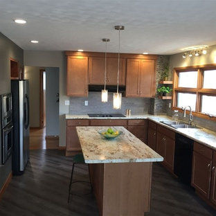Photo of a mid-sized midcentury l-shaped kitchen in Cedar Rapids with a double-bowl sink, shaker cabinets, brown cabinets, grey splashback, stainless steel appliances, with island, brown floor, laminate benchtops, stone tile splashback and vinyl floors.