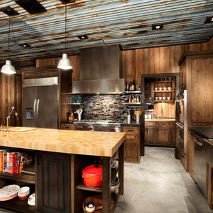 Open concept kitchen - rustic l-shaped concrete floor and gray floor open concept kitchen idea with a farmhouse sink, shaker cabinets, medium tone wood cabinets, wood countertops, brown backsplash, mosaic tile backsplash, stainless steel appliances and an island