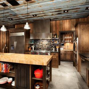 ラスティックスタイルのおしゃれなキッチン (エプロンフロントシンク、シェーカースタイル扉のキャビネット、中間色木目調キャビネット、木材カウンター、茶色いキッチンパネル、モザイクタイルのキッチンパネル、シルバーの調理設備の、コンクリートの床、グレーの床) の写真
