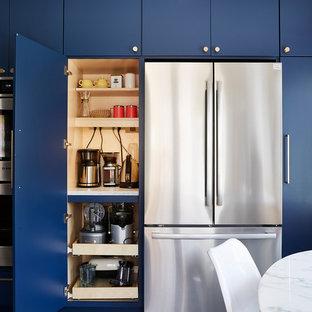 ミネアポリスの中サイズのミッドセンチュリースタイルのおしゃれなキッチン (アンダーカウンターシンク、フラットパネル扉のキャビネット、青いキャビネット、クオーツストーンカウンター、白いキッチンパネル、セメントタイルのキッチンパネル、シルバーの調理設備、セメントタイルの床、アイランドなし、グレーの床、黒いキッチンカウンター) の写真