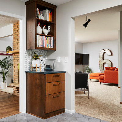 Example of a mid-sized 1960s u-shaped cement tile floor and gray floor enclosed kitchen design in Minneapolis with an undermount sink, flat-panel cabinets, medium tone wood cabinets, quartz countertops, white backsplash, cement tile backsplash, stainless steel appliances, no island and black countertops