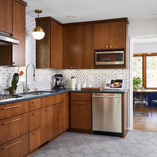 ミネアポリスの中サイズのミッドセンチュリースタイルのおしゃれなキッチン (アンダーカウンターシンク、フラットパネル扉のキャビネット、中間色木目調キャビネット、クオーツストーンカウンター、白いキッチンパネル、セメントタイルのキッチンパネル、シルバーの調理設備、セメントタイルの床、アイランドなし、グレーの床、黒いキッチンカウンター) の写真