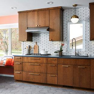 Mid-sized mid-century modern eat-in kitchen photos - Example of a mid-sized 1950s l-shaped cement tile floor and gray floor eat-in kitchen design in Minneapolis with an undermount sink, flat-panel cabinets, quartz countertops, white backsplash, cement tile backsplash, stainless steel appliances, no island, black countertops and dark wood cabinets