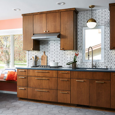 Example of a mid-sized 1950s l-shaped cement tile floor and gray floor eat-in kitchen design in Minneapolis with an undermount sink, flat-panel cabinets, quartz countertops, white backsplash, cement tile backsplash, stainless steel appliances, no island, black countertops and dark wood cabinets