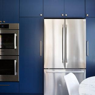 Inspiration för avskilda, mellanstora 60 tals svart u-kök, med en undermonterad diskho, släta luckor, blå skåp, bänkskiva i kvarts, vitt stänkskydd, stänkskydd i cementkakel, rostfria vitvaror, cementgolv och grått golv