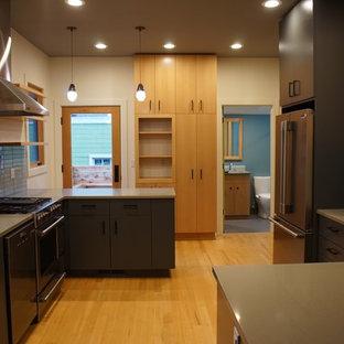 Geschlossene, Große Mid-Century Küche in L-Form mit Unterbauwaschbecken, flächenbündigen Schrankfronten, grauen Schränken, Quarzwerkstein-Arbeitsplatte, Küchenrückwand in Blau, Rückwand aus Glasfliesen, Küchengeräten aus Edelstahl, braunem Holzboden und Halbinsel in Portland