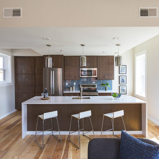 This is an example of a small midcentury single-wall eat-in kitchen in Cincinnati with flat-panel cabinets, dark wood cabinets, laminate benchtops, blue splashback, glass tile splashback, stainless steel appliances, light hardwood floors, with island, an undermount sink and brown floor.