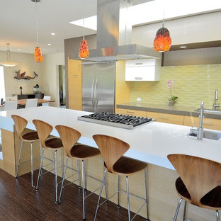 Photo of a large midcentury galley eat-in kitchen in San Francisco with stainless steel appliances, yellow splashback, glass tile splashback, light wood cabinets, flat-panel cabinets, an undermount sink, quartz benchtops, dark hardwood floors, with island and brown floor.