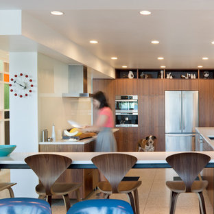 This is an example of a modern u-shaped kitchen/diner in Seattle with flat-panel cabinets, glass sheet splashback, stainless steel appliances, dark wood cabinets, a submerged sink, granite worktops, white splashback, a breakfast bar, cork flooring and beige floors.