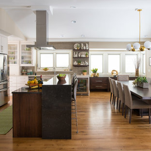 Example of a mid-sized transitional l-shaped medium tone wood floor and brown floor eat-in kitchen design in Minneapolis with an undermount sink, white cabinets, marble countertops, brown backsplash, porcelain backsplash, stainless steel appliances, an island, recessed-panel cabinets and beige countertops