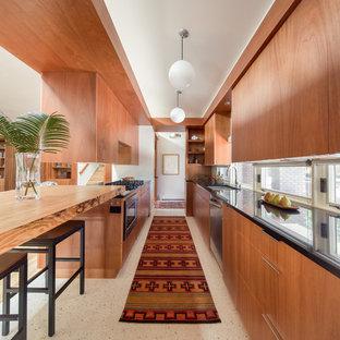 Idéer för att renovera ett avskilt, litet 50 tals svart svart parallellkök, med släta luckor, skåp i mellenmörkt trä, granitbänkskiva, terrazzogolv och en halv köksö