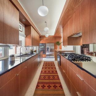 Geschlossene, Zweizeilige, Kleine Mid-Century Küche mit flächenbündigen Schrankfronten, hellbraunen Holzschränken, Granit-Arbeitsplatte, Terrazzo-Boden, Halbinsel, schwarzer Arbeitsplatte, Doppelwaschbecken, Rückwand-Fenster, Küchengeräten aus Edelstahl und weißem Boden in Denver