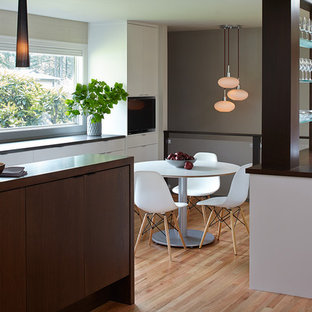 Design ideas for a large midcentury l-shaped eat-in kitchen in Portland with an undermount sink, flat-panel cabinets, dark wood cabinets, quartzite benchtops, white splashback, porcelain splashback, stainless steel appliances, light hardwood floors and with island.