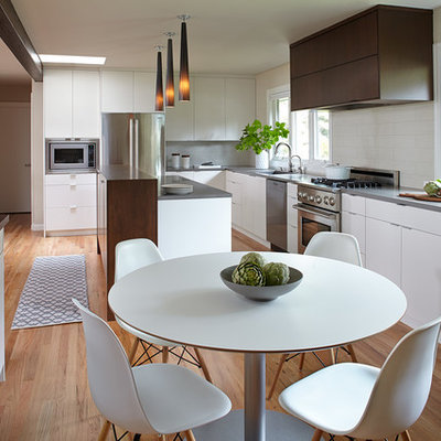 Example of a large trendy l-shaped medium tone wood floor eat-in kitchen design in Portland with an undermount sink, flat-panel cabinets, white cabinets, quartzite countertops, white backsplash, porcelain backsplash, stainless steel appliances and an island