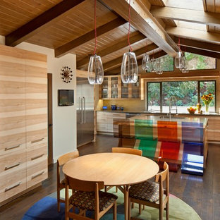 Mid-sized midcentury l-shaped eat-in kitchen in Los Angeles with flat-panel cabinets, light wood cabinets, yellow splashback, stainless steel appliances, an undermount sink, solid surface benchtops, matchstick tile splashback, dark hardwood floors and with island.
