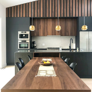 Design ideas for a mid-sized midcentury galley open plan kitchen in Toronto with an undermount sink, flat-panel cabinets, black cabinets, tile benchtops, beige splashback, porcelain splashback, stainless steel appliances, light hardwood floors, with island and black benchtop.