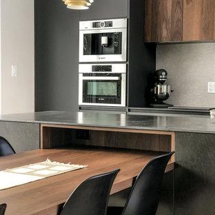 トロントの中くらいのミッドセンチュリースタイルのおしゃれなキッチン (アンダーカウンターシンク、フラットパネル扉のキャビネット、黒いキャビネット、タイルカウンター、ベージュキッチンパネル、磁器タイルのキッチンパネル、シルバーの調理設備、淡色無垢フローリング、黒いキッチンカウンター) の写真