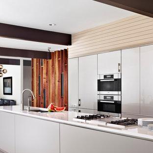 オースティンの広いコンテンポラリースタイルのおしゃれなキッチン (アンダーカウンターシンク、フラットパネル扉のキャビネット、人工大理石カウンター、白いキャビネット、白いキッチンパネル、シルバーの調理設備、セラミックタイルの床) の写真