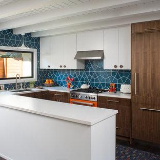 Idéer för ett mellanstort 60 tals vit kök, med en undermonterad diskho, släta luckor, skåp i mellenmörkt trä, bänkskiva i kvarts, blått stänkskydd, stänkskydd i keramik, färgglada vitvaror, mörkt trägolv, en halv köksö och brunt golv