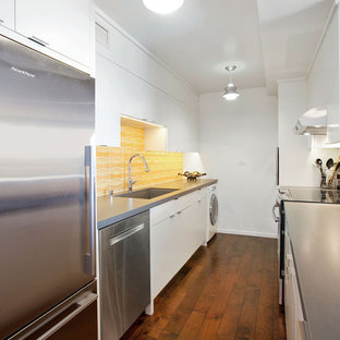 Small modern enclosed kitchen ideas - Inspiration for a small modern galley medium tone wood floor and brown floor enclosed kitchen remodel in San Francisco with a drop-in sink, flat-panel cabinets, white cabinets, quartz countertops, white backsplash, ceramic backsplash, stainless steel appliances and no island