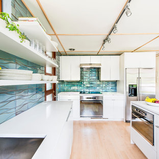 Mid-sized midcentury u-shaped kitchen in Los Angeles with a drop-in sink, flat-panel cabinets, white cabinets, quartz benchtops, blue splashback, ceramic splashback, stainless steel appliances, light hardwood floors and a peninsula.