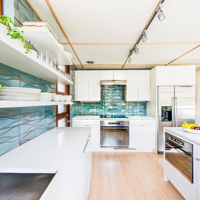 Inspiration for a mid-sized mid-century modern u-shaped light wood floor kitchen remodel in Los Angeles with a drop-in sink, flat-panel cabinets, white cabinets, quartz countertops, blue backsplash, ceramic backsplash, stainless steel appliances and a peninsula