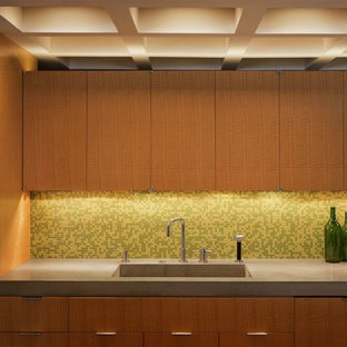 Mid-sized eat-in kitchen ideas - Example of a mid-sized single-wall terra-cotta floor eat-in kitchen design in New York with an undermount sink, flat-panel cabinets, dark wood cabinets, concrete countertops, green backsplash, ceramic backsplash, stainless steel appliances and an island