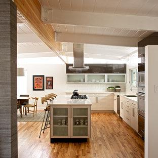 デンバーの中サイズのモダンスタイルのおしゃれなキッチン (フラットパネル扉のキャビネット、白いキャビネット、白いキッチンパネル、サブウェイタイルのキッチンパネル、シルバーの調理設備) の写真