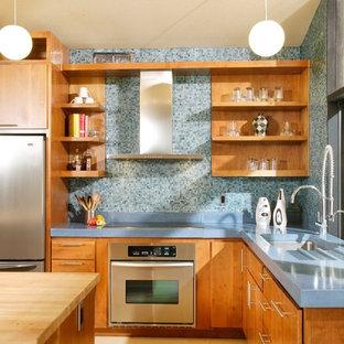 Bild på ett 50 tals blå blått kök, med bänkskiva i betong, släta luckor, skåp i mellenmörkt trä, blått stänkskydd, stänkskydd i mosaik och rostfria vitvaror