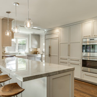 Example of a mid-sized transitional galley medium tone wood floor open concept kitchen design in Dallas with a farmhouse sink, shaker cabinets, gray cabinets, quartzite countertops, gray backsplash, ceramic backsplash, stainless steel appliances and a peninsula