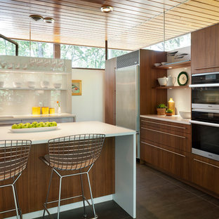 Mid-sized midcentury l-shaped kitchen pantry in DC Metro with an undermount sink, flat-panel cabinets, white cabinets, laminate benchtops, white splashback, with island and brown floor.