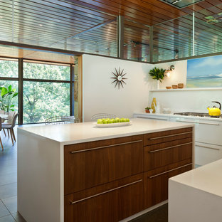 This is an example of a mid-sized midcentury l-shaped kitchen pantry in DC Metro with an undermount sink, flat-panel cabinets, white cabinets, laminate benchtops, white splashback, with island and brown floor.
